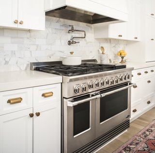 An Interior Designer's Streamlined Kitchen - Photo 2 of 7 - Dual Flow Burners deliver rapid, even heating that can reach up to 23,500 BTU, and the cooktop offers a total of up to 116,000 BTU with burners simmering at 140 degrees. A power griddle reaches 18,000 BTU.  The dials offer precise control with LED halos that turn white, orange, and red to indicate heating up, preheated, and self-cleaning modes, respectively.