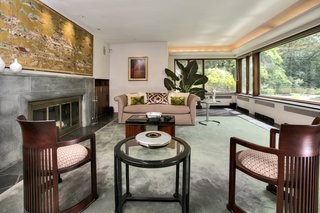 A Curvaceous Connecticut Home Asks $2.6M - Photo 5 of 8 - The living room's fieldstone and aluminum fireplace includes a hidden wood bin that is accessible from outside, keeping the homeowner supplied throughout winter.