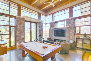 From the living room, thick oak stair treads suspended on steel stringers descend to the game room, where a walnut bar, Craftsman pool table, and fireplace set the scene for entertaining and lounging.