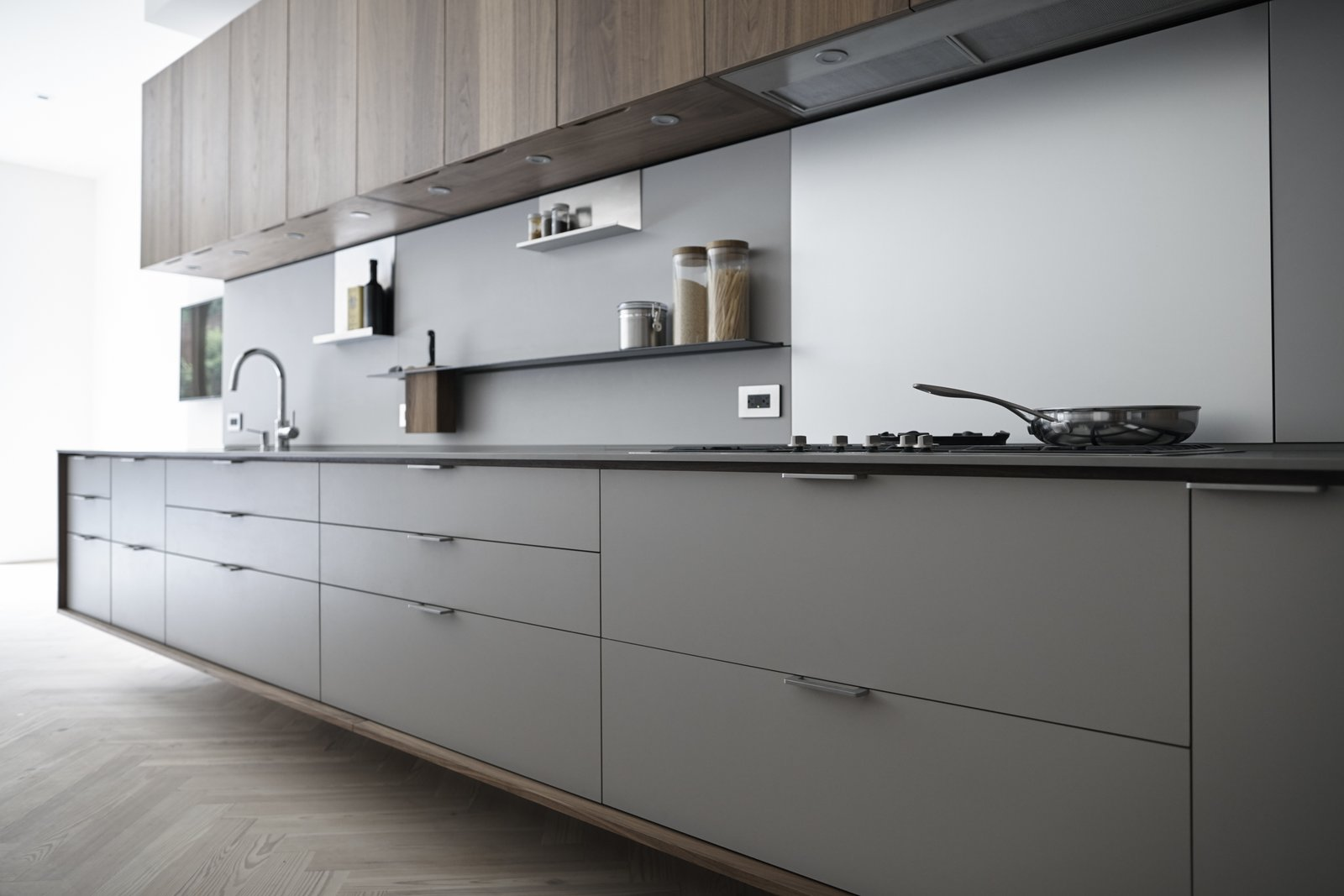 In a Henrybuilt kitchen system, every detail helps orchestrate a streamlined experience. For example, the pulls above protrude to match the plane of the counter and end panels. Drain fields are milled onto work surfaces to fit custom cutting boards and colanders, and low energy LED lights are morticed into the bottom of wall units, which have scoops instead of handles.  Photo 2 of 9 in The Whole House System That Unifies Every Room