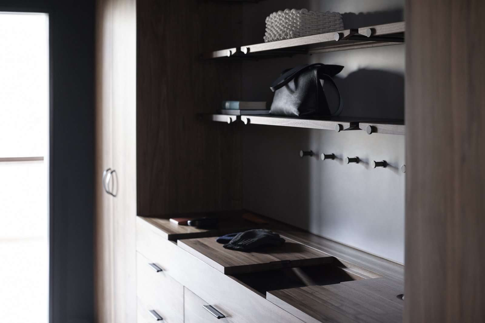 The Wardrobe System features sliding wooden valet trays, leather lined storage compartments, custom interior felt door pockets, handcrafted leather pulls, and an integrated laundry hamper. The Whole House System That Unifies Every Room - Photo 8 of 9