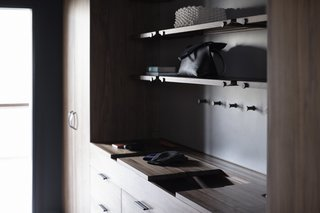 The Whole House System That Unifies Every Room - Photo 7 of 8 - The Wardrobe System features sliding wooden valet trays, leather lined storage compartments, custom interior felt door pockets, handcrafted leather pulls, and an integrated laundry hamper.