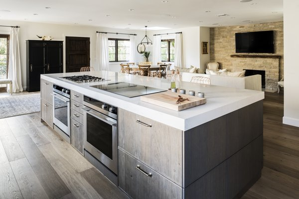 The gas and induction cooktop, along with the two ovens below, face the bar seating at the kitchen island, allowing Lefebvre to interact with his guests while preparing meals.  Photo 7 of 8 in Chef Ludo Lefebvre's Modern Kitchen With Rustic Roots