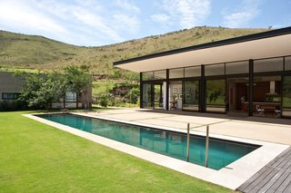 This South African Villa Lets You Bask in Divine Views - Photo 3 of 9 - The pool stretches across a rolling lawn that ends at the foot of the wooded mountains.