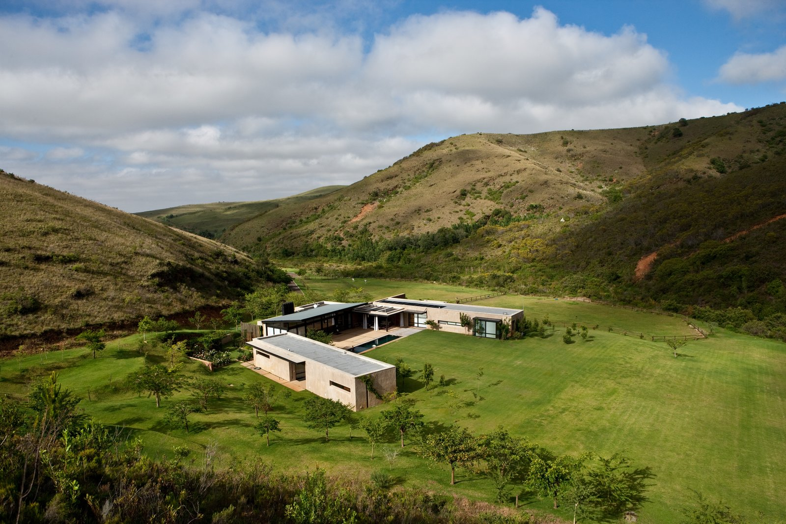 Guests can relax by the pool and soak in the views or hike into the mountains, following a creek into an ancient forest. Tagged: Outdoor, Slope, Shrubs, Trees, Back Yard, Grass, and Field.  Photo 2 of 10 in This South African Villa Lets You Bask in Divine Views