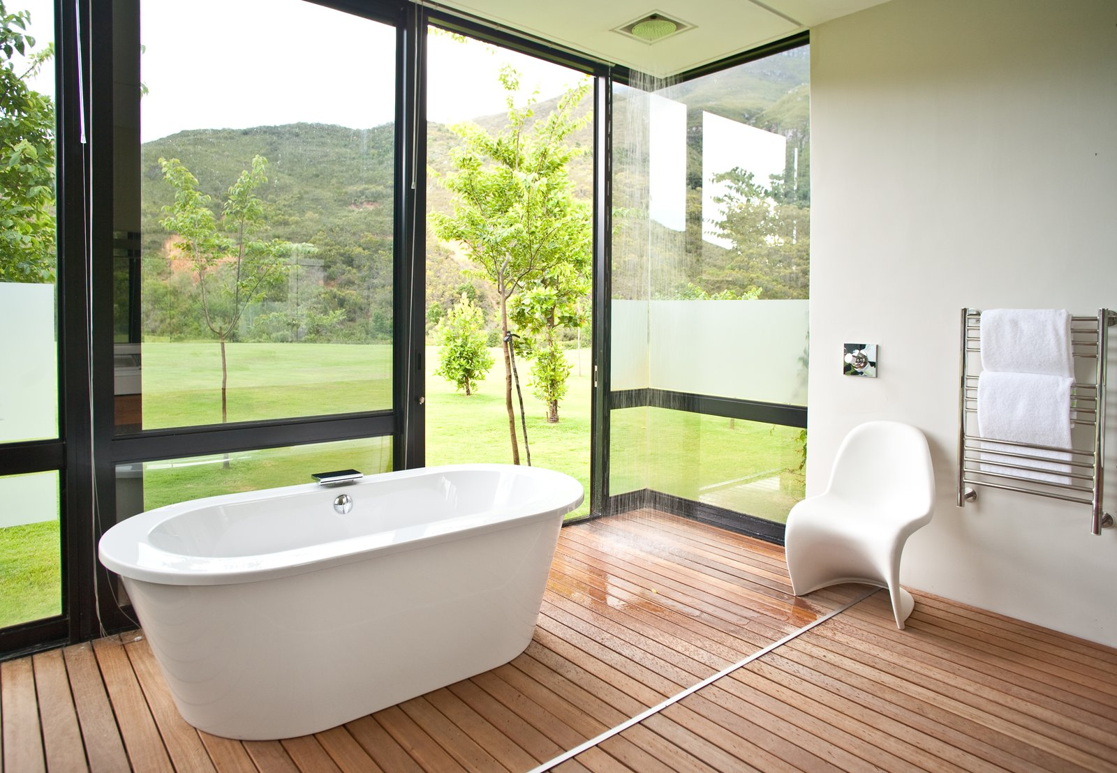 The guest bathrooms are outfitted with showers and tubs that feel close to nature. Tagged: Bath Room, Open Shower, Medium Hardwood Floor, Soaking Tub, and Freestanding Tub.  Photo 7 of 10 in This South African Villa Lets You Bask in Divine Views