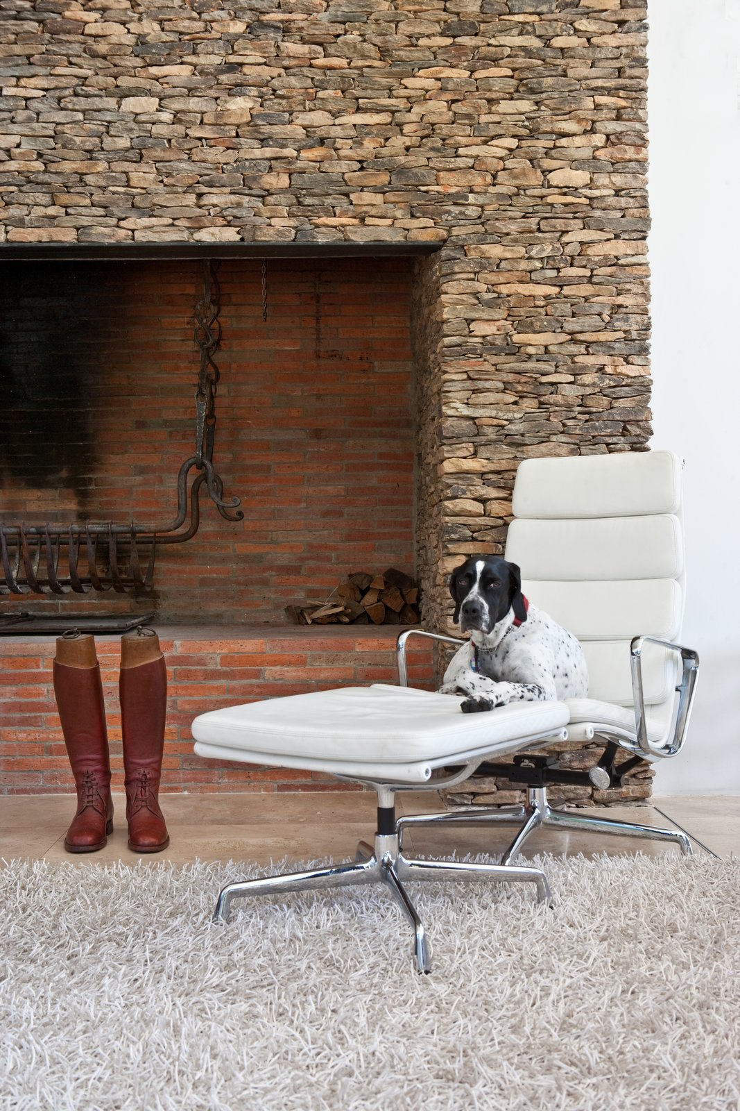 In the living area, a dry packet stone fireplace frames a fire grate that was forged by an expert blacksmith. Tagged: Living Room, Wood Burning Fireplace, Rug Floor, Standard Layout Fireplace, Ottomans, and Recliner.  Photo 17 of 25 in Leap Into the Year of the Dog With These 25 Pups in the Modern World from This South African Villa Lets You Bask in Divine Views