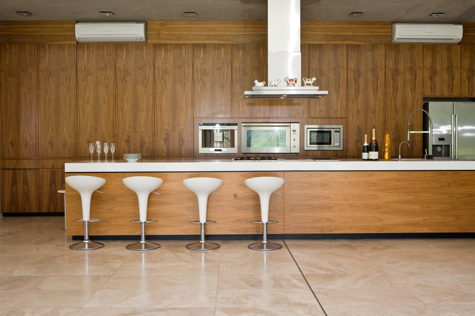 Herman and his wife love to cook for and entertain their guests. They also have a great selection of South African wine and malt whiskey. Tagged: Kitchen, Refrigerator, Range, Ceiling Lighting, Microwave, and Range Hood.  Photo 5 of 10 in This South African Villa Lets You Bask in Divine Views