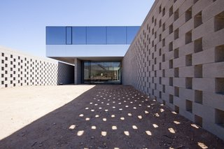 This Sleek Desert Home Seems to Melt Into the Sky - Photo 3 of 12 - Concrete block walls allow light and air to pass into the garden while maintaining a screen of privacy.