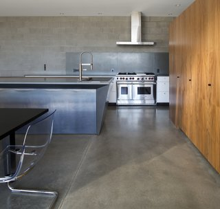 This Sleek Desert Home Seems to Melt Into the Sky - Photo 5 of 12 - The downstairs communal living spaces flow freely between kitchen, dining room, and living room. Concrete block walls and polished concrete floors emphasize the heavy materiality that supports the visual lightness of the upper story.