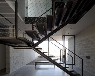 This Sleek Desert Home Seems to Melt Into the Sky - Photo 4 of 12 - The staircase remains open in form, helping to visually knit the entryway's garden into the living space while providing a structural focus.