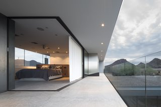 This Sleek Desert Home Seems to Melt Into the Sky - Photo 9 of 12 - A corner Multi-Slide Door transitions the master bedroom onto the patio, allowing the Staabs to sleep en plein air.