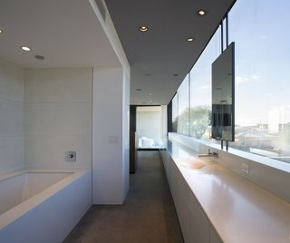 This Sleek Desert Home Seems to Melt Into the Sky - Photo 8 of 12 - The master bathroom and dressing room join the master bedroom as one open suite.
