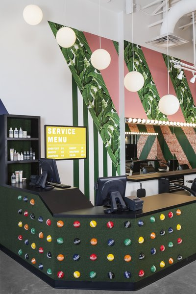Artificial turf and croquet balls add texture and personality to the reception desk.