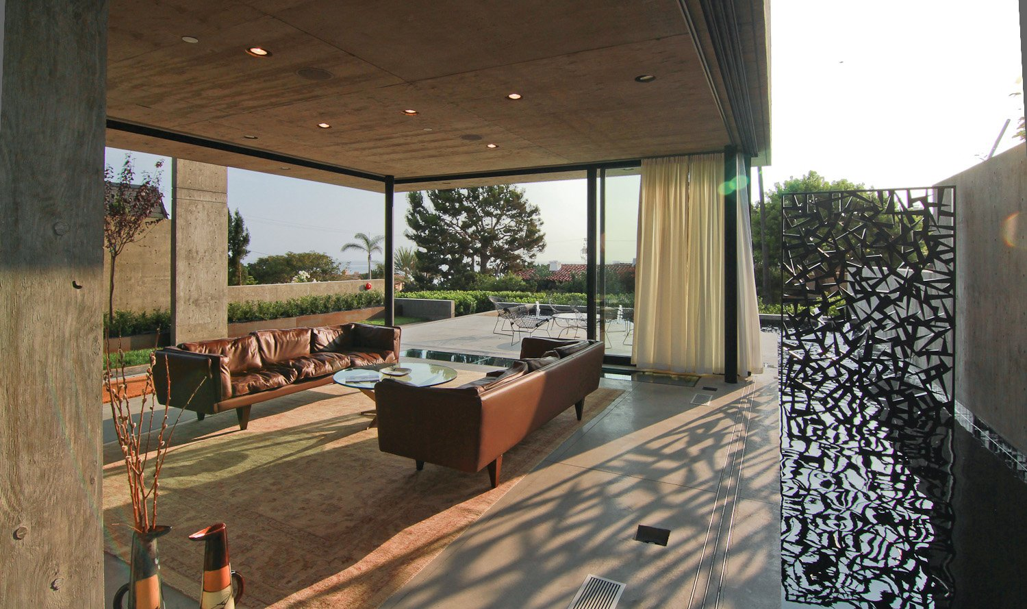 Multi-Slide Doors by Western Window Systems retract and allow the living room to enjoy the offshore breeze. The pool extends along one side, allowing the homeowners to feel as though they are floating on water.