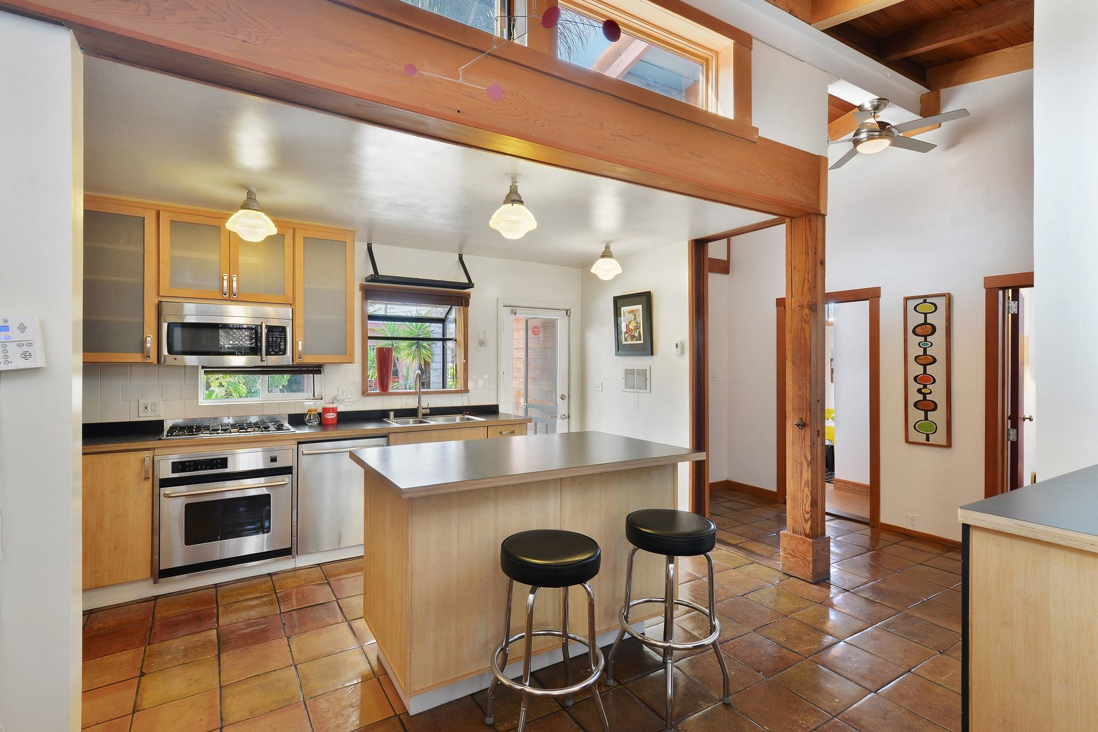 Apart from the side-by-side bathrooms, the layout of the home doesn't reflect its commercial beginnings. The kitchen, which features Saltillo tile flooring, used to be a back office.  Photo 5 of 12 in Artists Need Apply: This Midcentury Home Comes With an All-Purpose Workshop for $949K