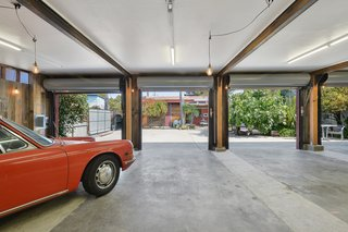 "Artists Need Apply: This Midcentury Home Comes With an All-Purpose Workshop for $949K - Photo 6 of 11 - ""You can set the whole place aglow,"" says Dean about entertaining in the courtyard. ""You can open all the [bay] doors with the collection of cars warmly lit by Edison bulbs."""
