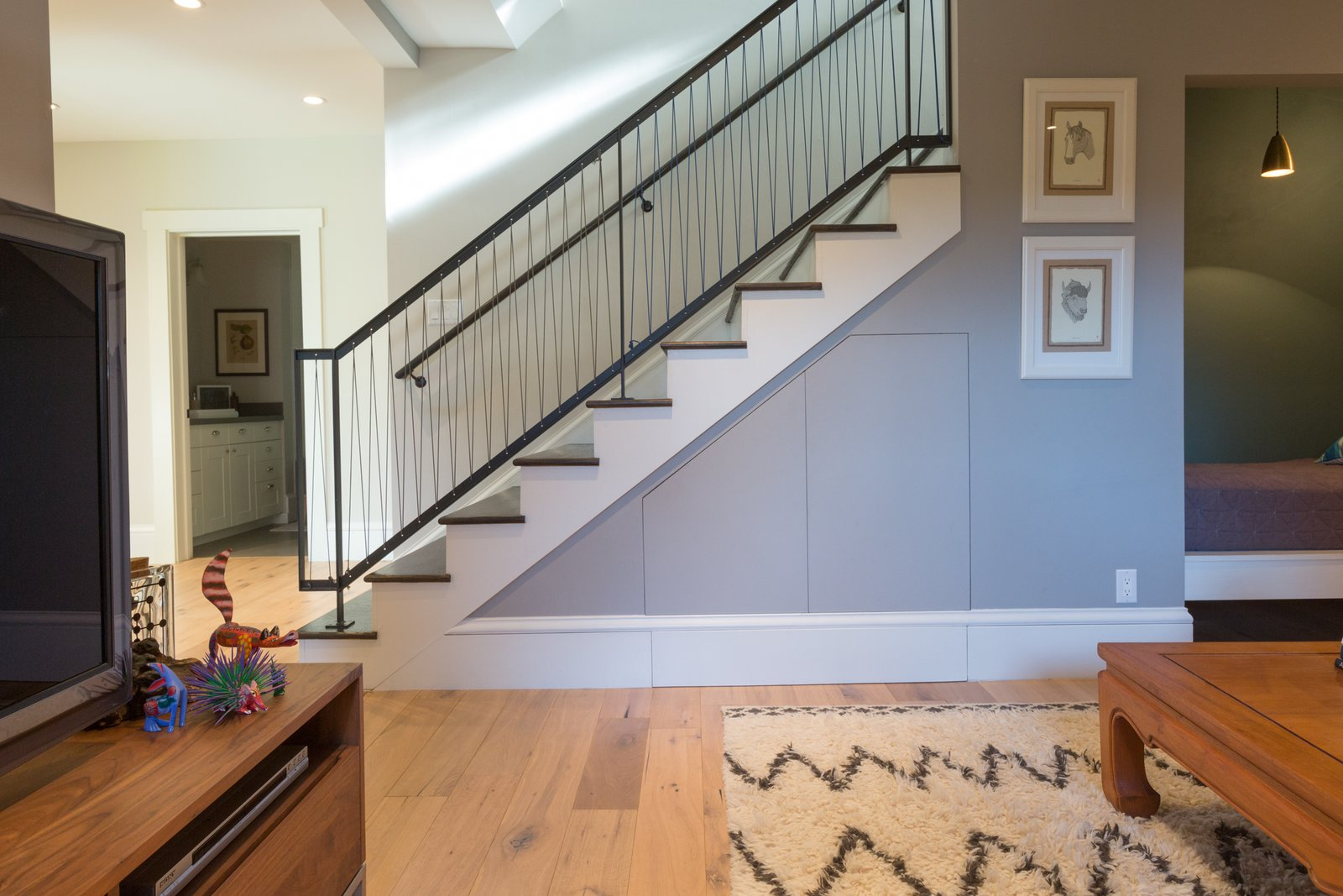 When connecting the basement level to the rest of the home, Wendi Sue chose a contemporary railing that would still cohere with the more traditional vernacular throughout. The custom steel stairwell features a matte black powder finish and pickets of tensioned military parachute cord. No Longer Off-Kilter - Photo 9 of 15