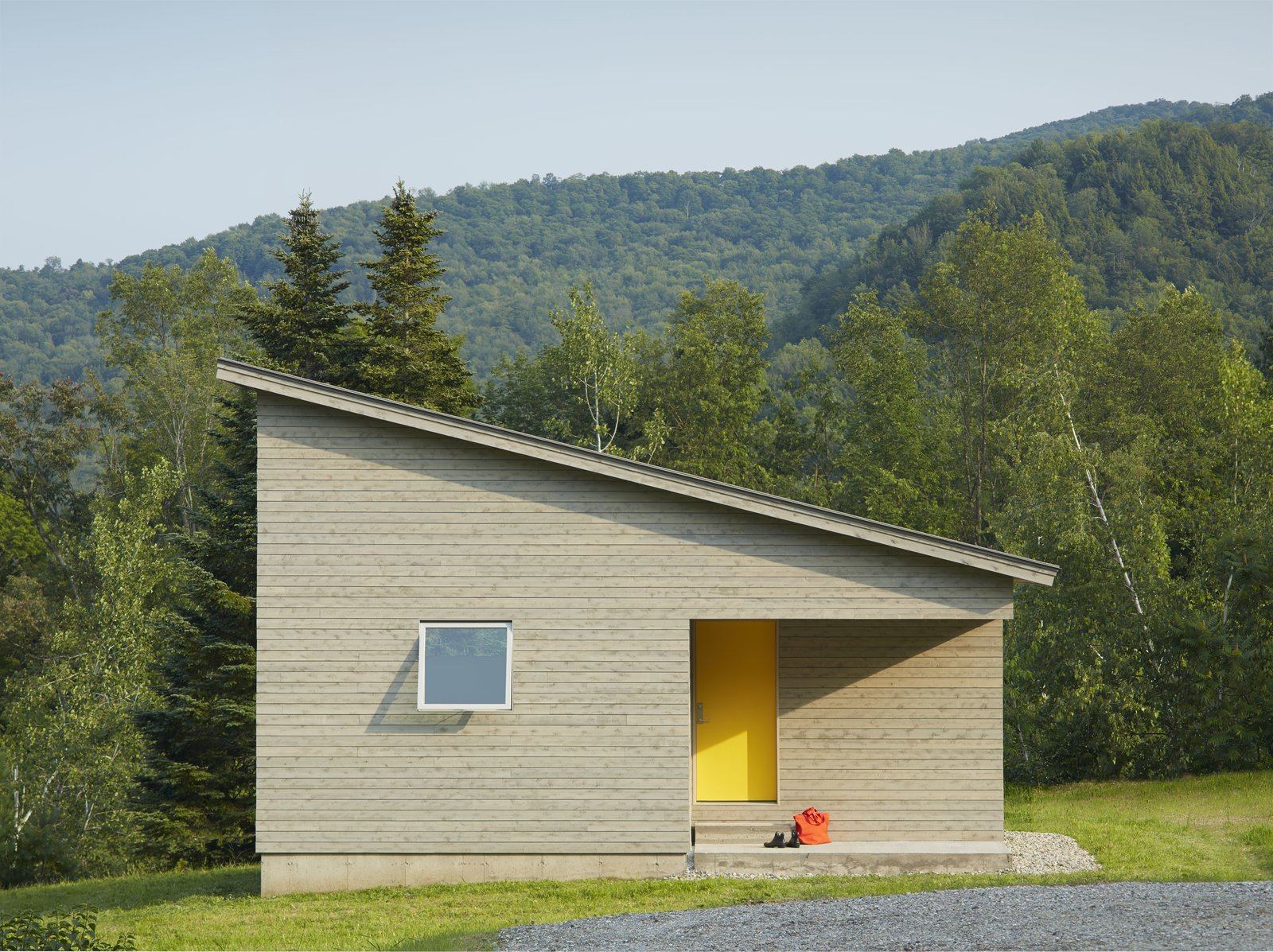 A cutaway in the structure's cubic shape forms a front porch, where a graphic yellow door welcomes visitors. The roof slopes downwards, holding more intimate spaces at its lower end.  Photo 2 of 5 in A Mini-Home With Mega-Views