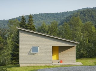 A Mini-Home With Mega-Views - Photo 1 of 4 - A cutaway in the structure's cubic shape forms a front porch, where a graphic yellow door welcomes visitors. The roof slopes downwards, holding more intimate spaces at its lower end.