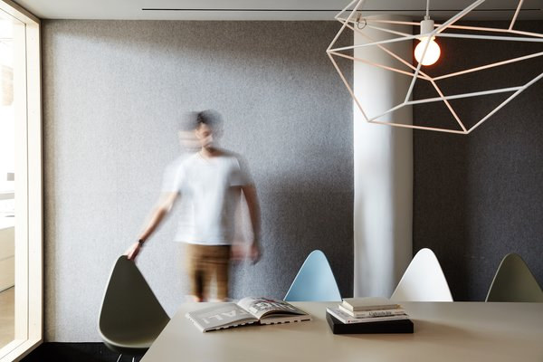 A large meeting room, equipped with Drop Chairs by Fritz Hansen and a sculptural Spica Light by Iacoli & McAllister, seats 14.