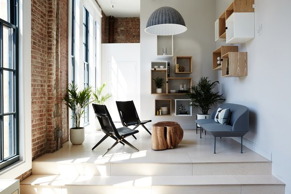 The library features a Muuto Oslo Sofa and Lassen Saxe Chairs. Exposed brick and generous windows are reminders of the warehouse setting.