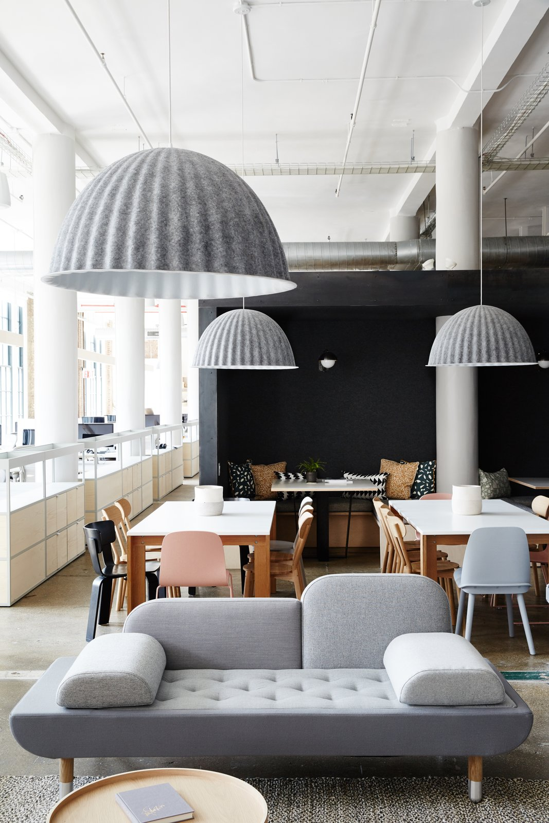 Muuto Under the Bell pendant lights are made from recycled plastic felt, which helps absorb noise and improve acoustics—a key feature in the open office.  Photo 12 of 12 in Space to Work, Room to Play