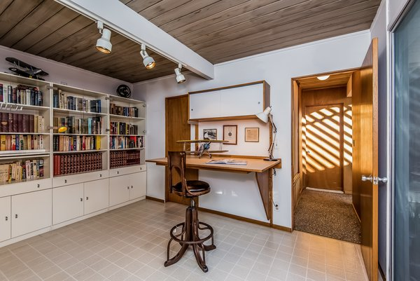 Built-in cabinets make this converted bedroom an ideal library.