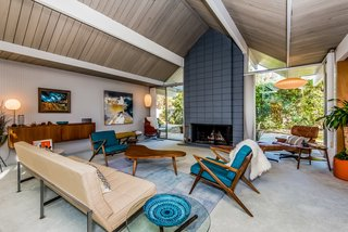 With Only One Previous Set of Owners, a Pristine Eichler Home Asks $799K - Photo 4 of 12 - The Cigar and Saucer Pendant Lamps by George Nelson and the 3-seat sofa and wall-mounted cabinet by Knoll are original—and also available for purchase. A cinderblock fireplace provides an inviting focal point.