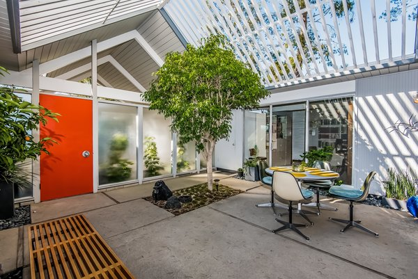 A covered entrance doubling as a carport leads to the square atrium, where cutouts in the concrete allow greenery to establish a sense of the outdoors. Enclosed in glass on all four sides, the atrium opens to the living room, multipurpose room, office and retreat.