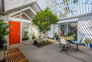 With Only One Previous Set of Owners, a Pristine Eichler Home Asks $799K - Photo 2 of 12 - A covered entrance doubling as a carport leads to the square atrium, where cutouts in the concrete allow greenery to establish a sense of the outdoors. Enclosed in glass on all four sides, the atrium opens to the living room, multipurpose room, office and retreat.