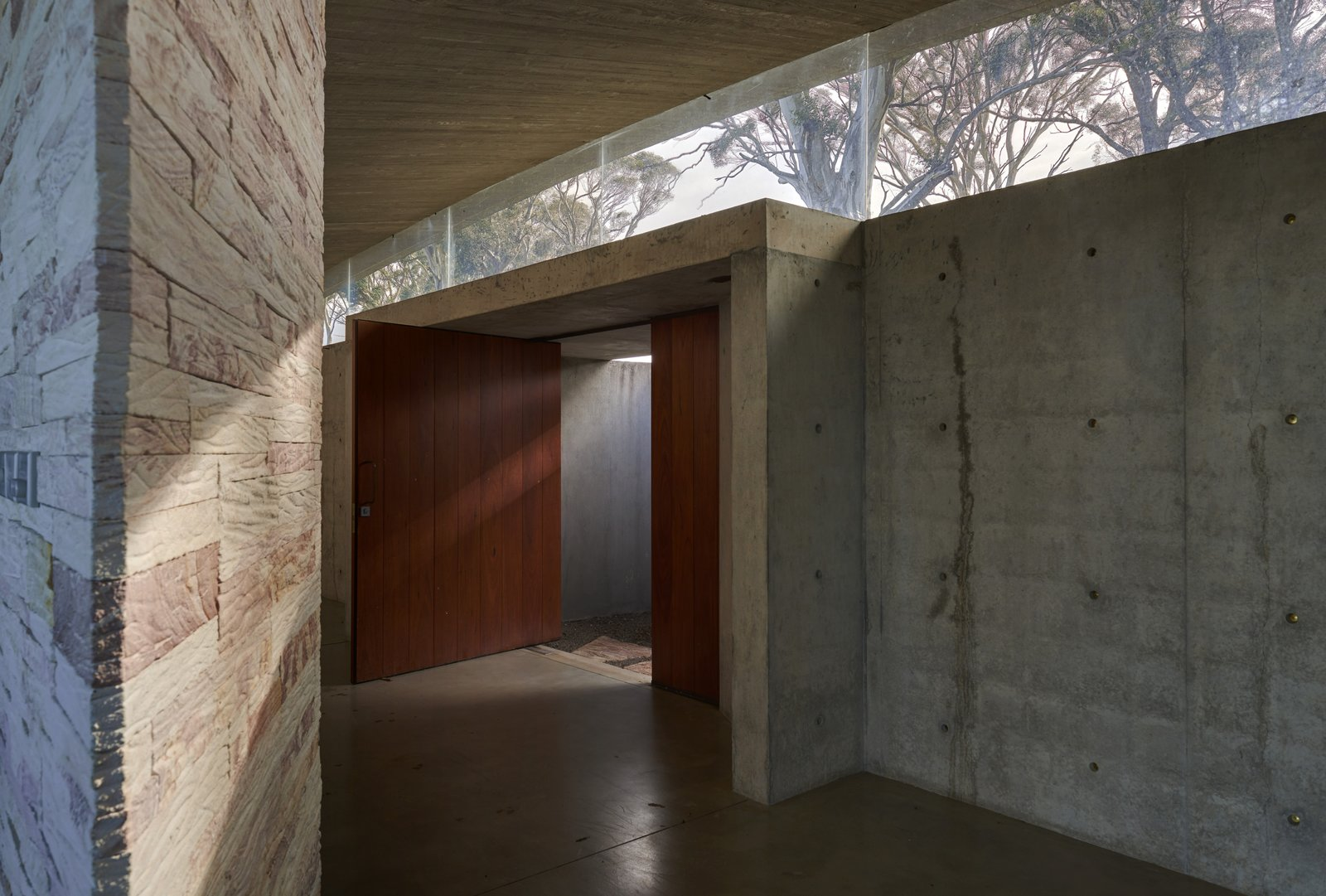 The entrance gallery provides a meditative sense of arrival and a counterpoint to the rest of the house, which is exposed on three sides. The Mudgee tiger skin stack stone wall was created over hundreds of hours by the project's dedicated builder and hand-crafter.  Photo 3 of 14 in An Internationally Celebrated Home in the Australian Backcountry Asks $9M