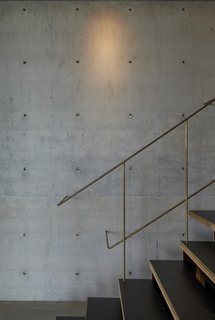 9 Unique Stair Railings - Photo 9 of 9 - The slim brass rods of the stair railing in this countryside house in Australia create a shimmering silhouette against the matte texture of the concrete wall. The rods die gracefully into the wall of the concrete, and the notes of brass are picked up by the concrete plugs inserted into the panels.