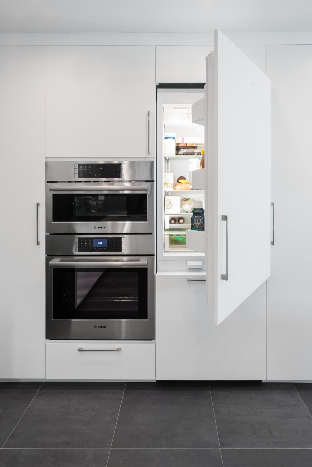 While the cooking appliances remain in the open, the Bosch refrigerator, freezer, and dishwasher are integrated into the cabinetry.  Photo 4 of 5 in Designed to Disappear: The Case For the Minimal Kitchen
