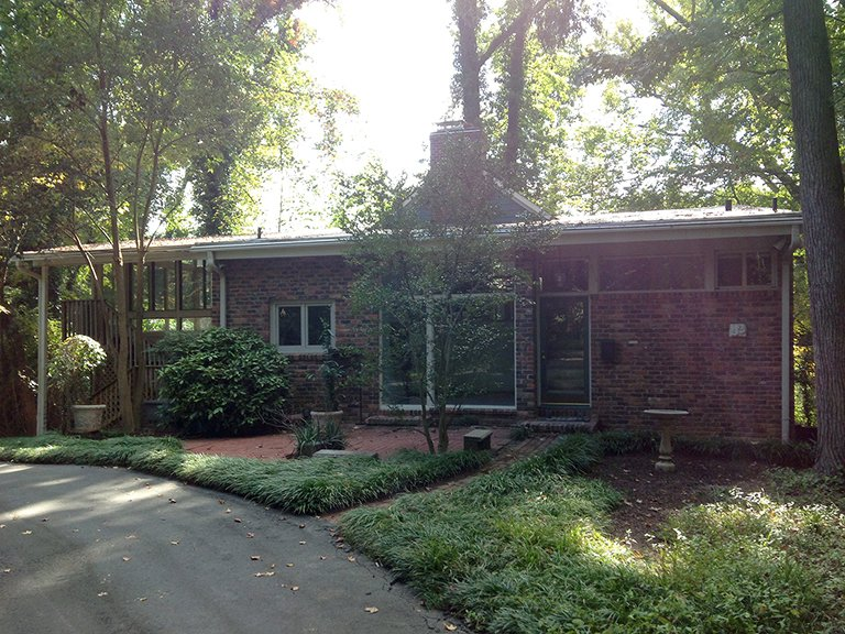"Architect Janice Finein shared a photo of the residence before the renovation. ""We changed the roof lines, extended the height of the brick wall, replaced the windows and doors, as well as added new materials and details,"" she says. Move Into This Midcentury Modern Revival in North Carolina For $1.2M - Photo 2 of 11"