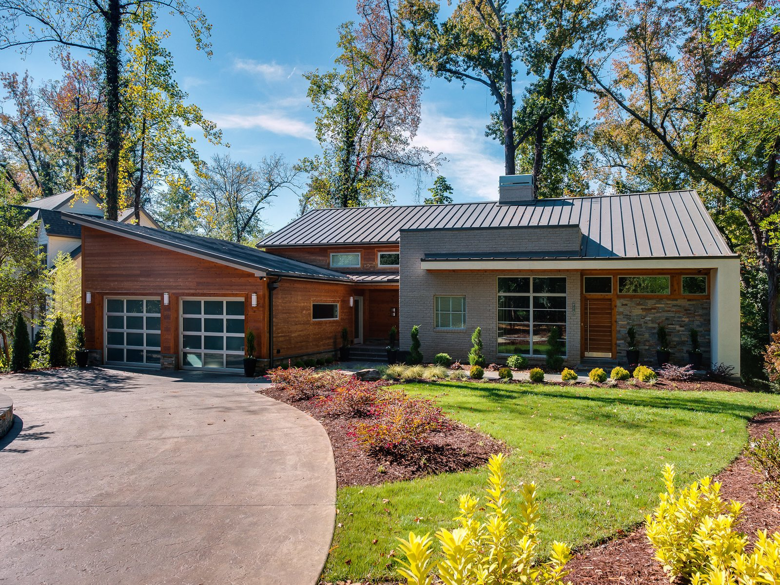 Western red cedar, natural stone, stucco, and brick form a warm exterior. The standing metal metal roof, under warranty through 2055, withstands winds up to 110 miles per hour. Automatic LED lighting illuminates the entry at night.  Photo 3 of 11 in Move Into This Midcentury Modern Revival in North Carolina For $1.2M