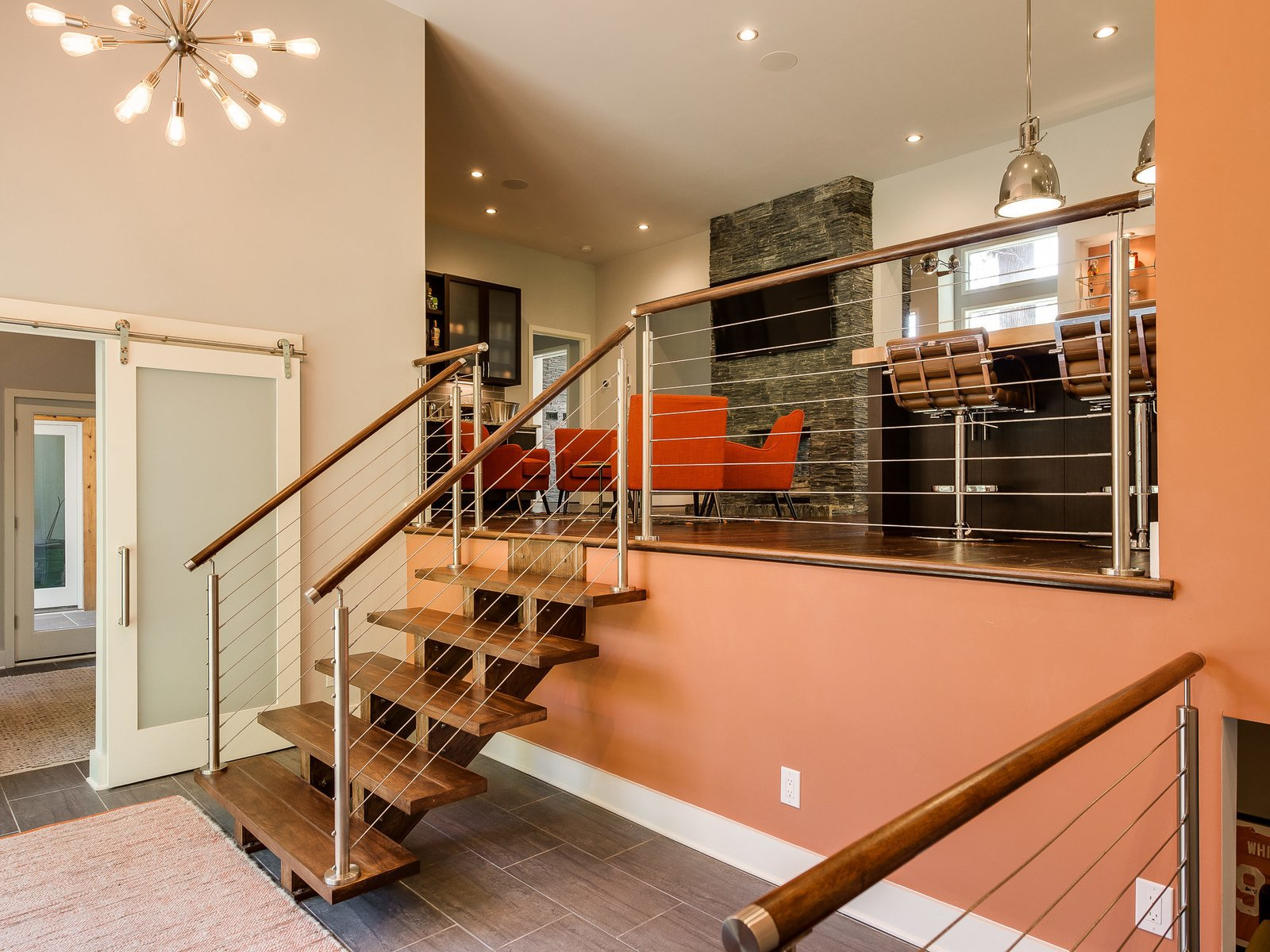 """""""My favorite feature is the entry of the home,"""" says Finein. """"It is where you see the greatest transformation, both inside and out."""" Hickory floating stairs and a stainless steel railing system lead to the upper floor. Through the frosted glass barn door is the office, which enjoys a granite countertop built-in desk."""