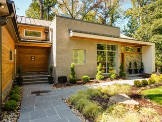 The landscaping features encore azaleas, arborvitae, and Japanese cypress. An oak forest in the backyard provides a sense of privacy and seclusion.