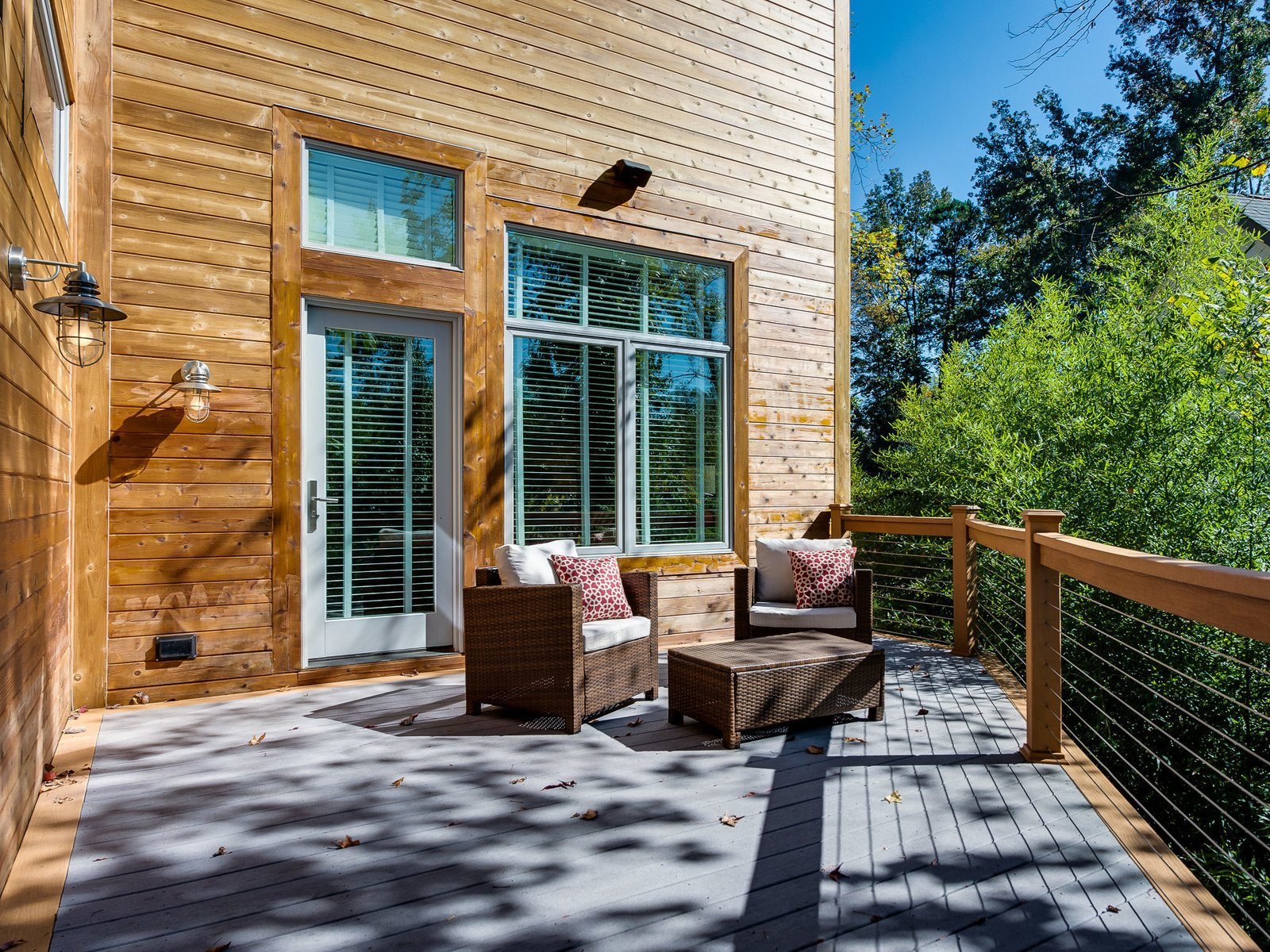 Approximately 516 square feet, the back deck is comprised of two-toned cedar and gray composite wood. Four all-weather speakers provide entertainment, and the reinforced left side allows for hot tub installation.  Photo 11 of 11 in Move Into This Midcentury Modern Revival in North Carolina For $1.2M