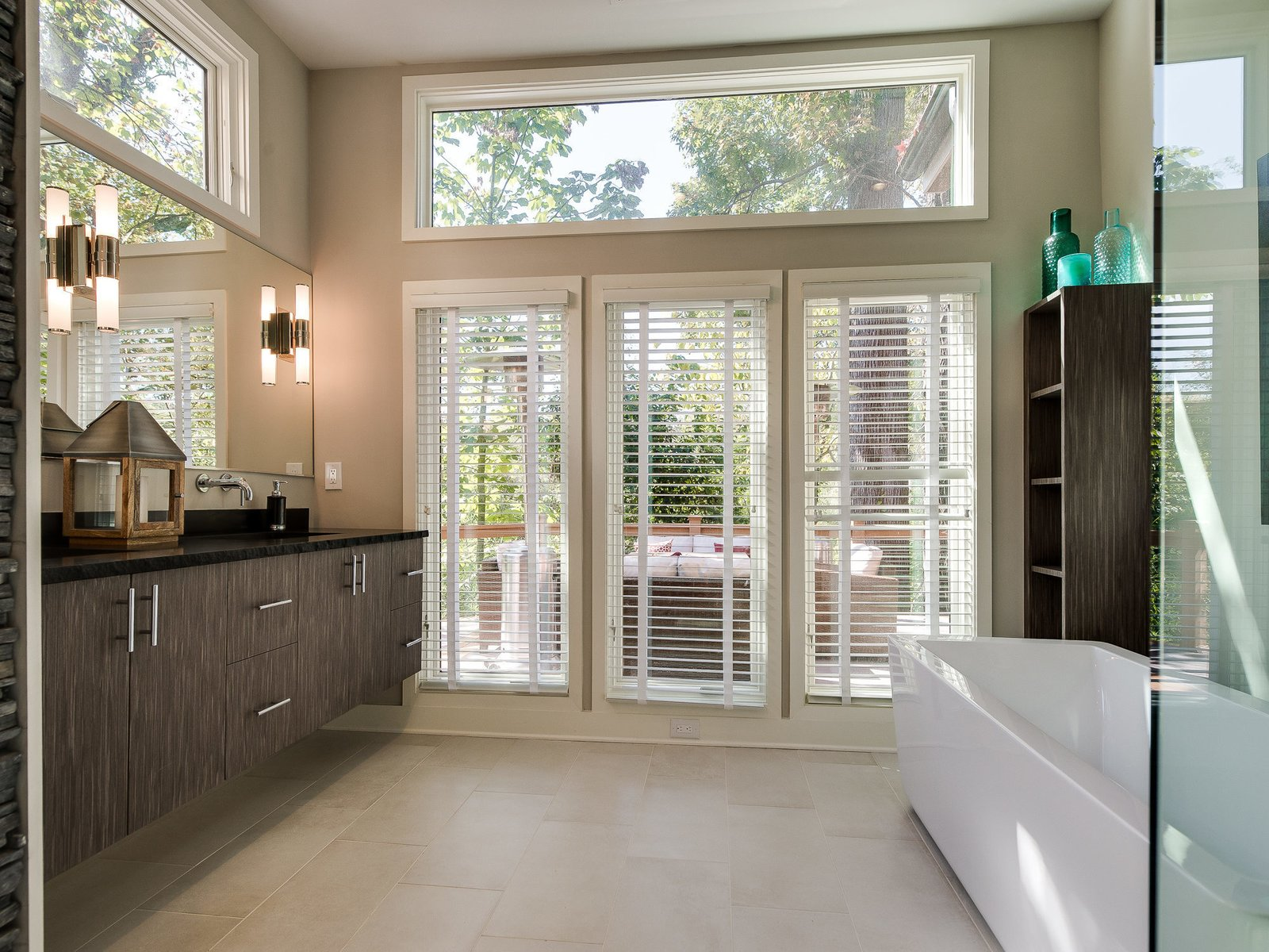 A frosted glass pocket door leads to the master bathroom, which enjoys a large free-standing tub and a floating double vanity.