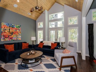On the other side of the fireplace is the great room, where a vaulted cedar ceiling, measuring 18 feet at its height, adds to the feeling of spaciousness. The French doors lead to the balcony.