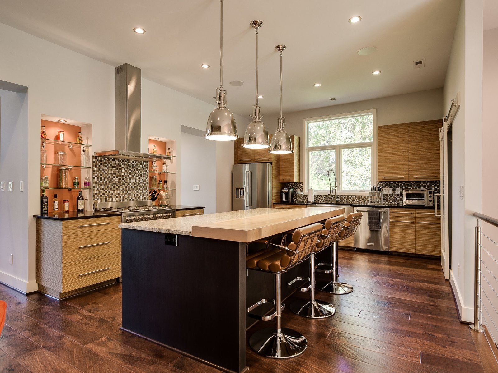 Custom Treefrog wood cabinets and quartz countertops outfit the kitchen, where a granite island with a built-in butcher block transitions into bar seating. Benson Pendants by Restoration Hardware hang above. Another frosted glass barn door leads to a walk-in pantry.  Photo 6 of 11 in Move Into This Midcentury Modern Revival in North Carolina For $1.2M