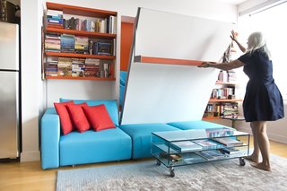 Two Film Industry Veterans Flip the Script With a Suburb-to-City Move - Photo 3 of 5 - Van Duren demonstrates the ease of lowering the Swing, a queen-size wall bed with nine-foot sofa and sliding chaise. Here, it integrates with a shelving system, which continues the apartment's quirky motif of orange and blue.