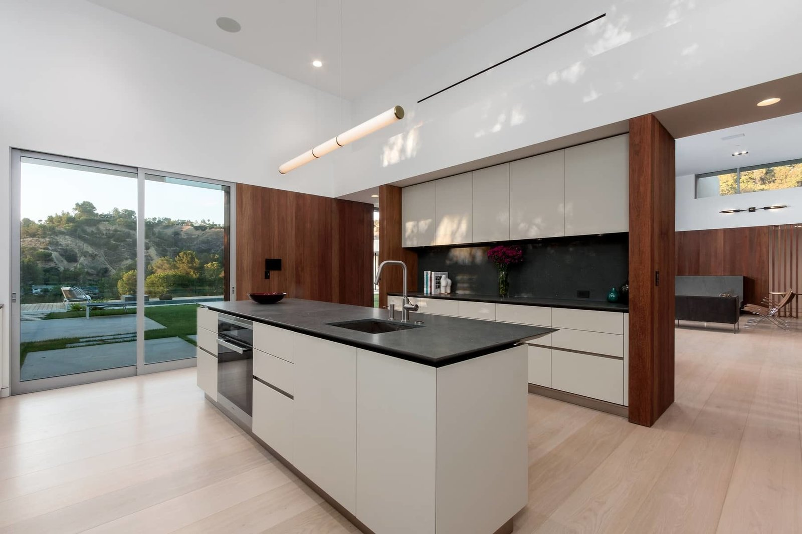 Boffi kitchen cabinets are a minimalist complement to Miele appliances, including a wine fridge and a built-in expresso machine. The Mini Endless pendant is by Roll & Hill.  Photo 5 of 10 in A Celeb-Worthy Home in Beverly Hills Asks $6.75M