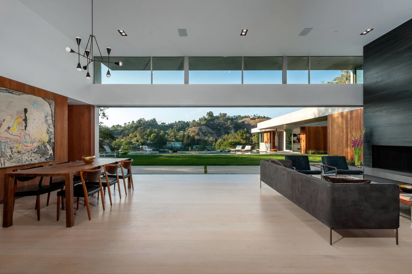 The open plan living and dining areas benefit from a long clerestory window, while sliding doors by Metal Window Corporation blur the boundary between interior and exterior.  Photo 4 of 10 in A Celeb-Worthy Home in Beverly Hills Asks $7.4M