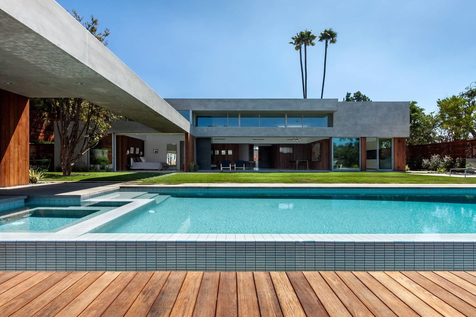 An extended wood terrace surrounds the pool, creating a courtyard setting.