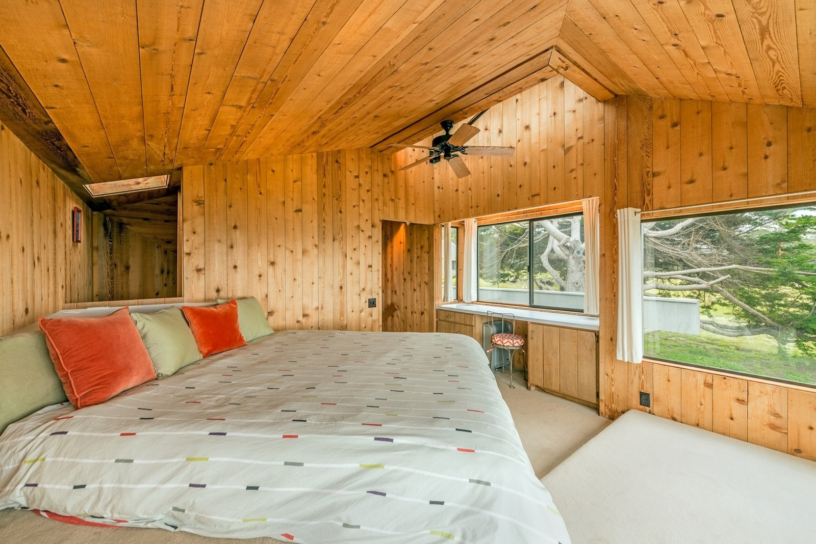 The angular master bedroom benefits from plenty of windows, including a skylight above a built-in vanity.  Photo 6 of 12 in Settle in the Celebrated Sea Ranch For Under $2.9M