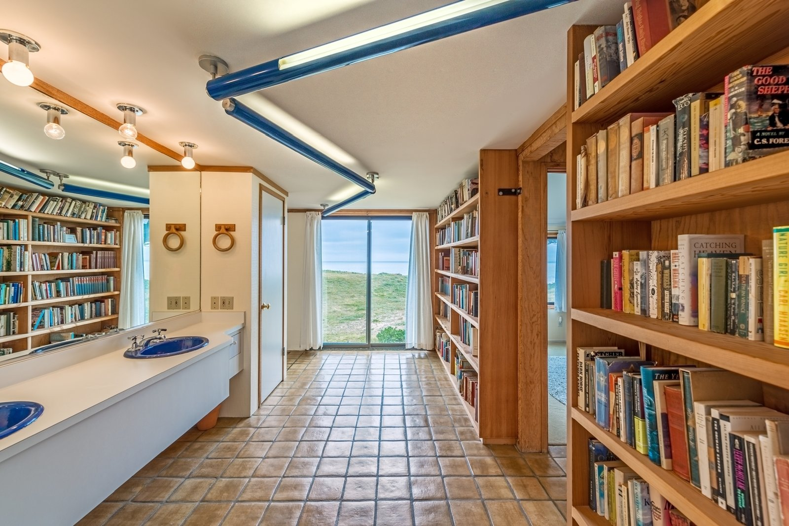 In keeping with Moore's whimsical design sense, a guest bathroom has its own library.