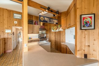 Settle in the Celebrated Sea Ranch For Under $2.9M - Photo 1 of 11 - Original wood paneling and tile flooring run throughout the house. The front entry leads into an integrated kitchen and dining space.