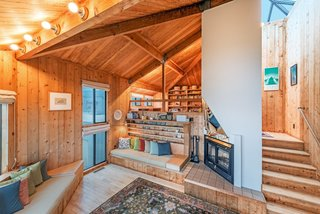 """Settle in the Celebrated Sea Ranch For Under $2.9M - Photo 3 of 11 - A favorite view of Owings' is looking up while lying on the living room rug. """"I am constantly astonished how Moore worked out the angles, with wood and steel and braces, all in plain view,"""" she says. A mirror hangs above the fireplace, reflecting the water. The stairs to the right lead to a multifunctional loft space, where the sunset is visible year-round."""